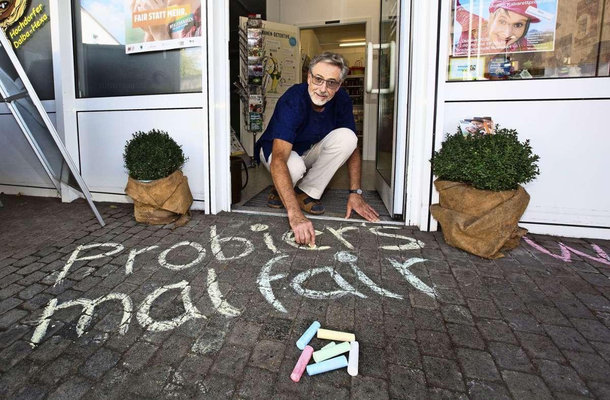 Gerhard Bäßler schreibt eine Kreide-Botschaft zu den Fairen Wochen. Foto: Ines Rudel