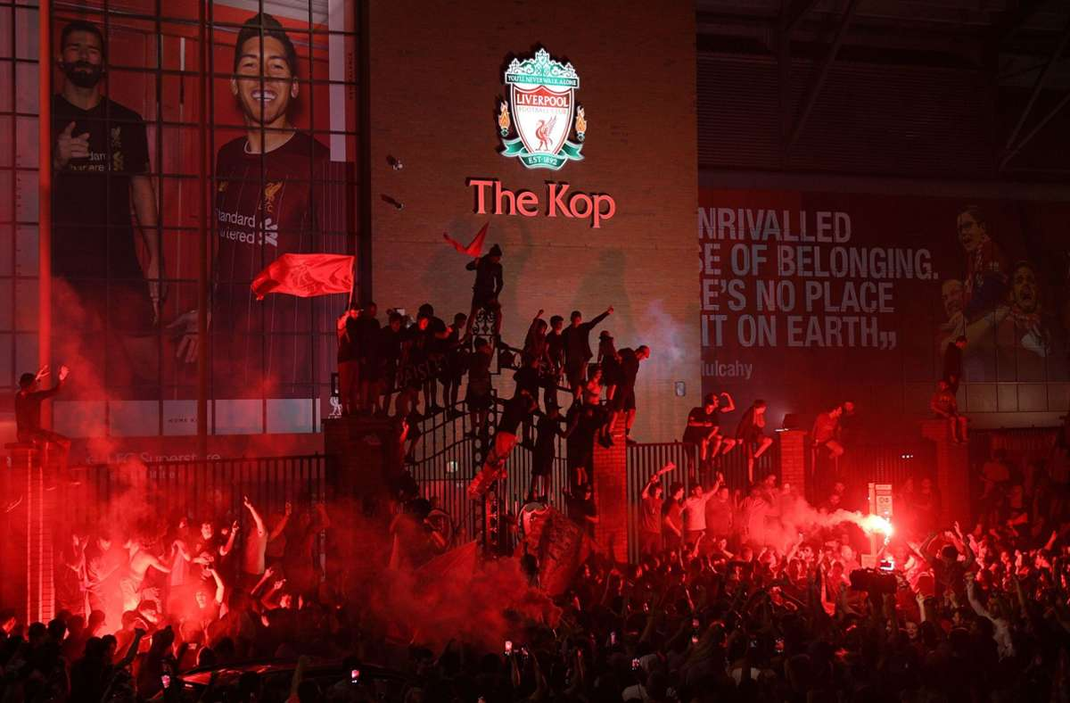Fans feiern die englische Meisterschaft vor und auf dem Zaun des Anfield Stadions. Foto: AFP/OLI SCARFF