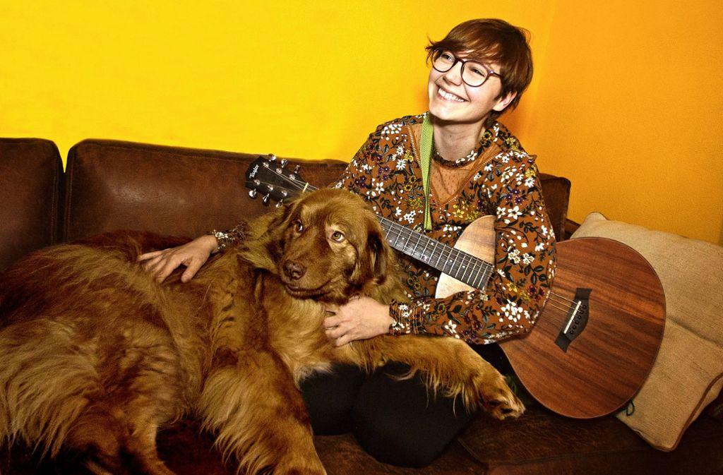 Beatrice  Bacher – hier mit Hund Tomte – hat sich das Gitarrespielen selbst beigebracht. Als klassische Liedermacherin sieht sie sich nicht. Foto: Ines Rudel