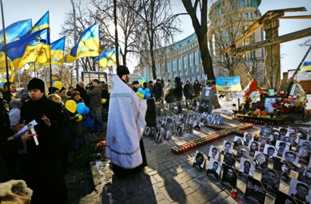 Ein orthodoxer Priester gedenkt mit Bürgern der Stadt Kiew der Menschen, die vor einem Jahr bei den Unruhen ums Leben kamen. Foto: AP
