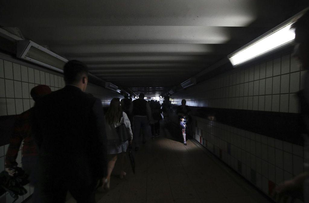 Menschen laufen am Freitag durch eine dunkle Unterführung in London. Foto: AP