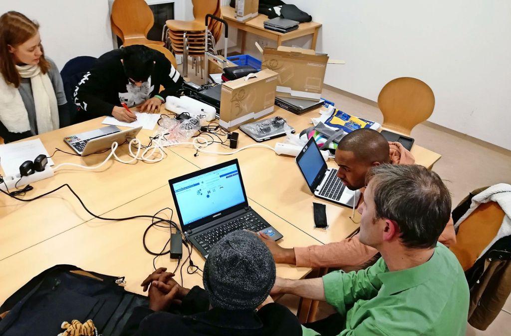 Thomas Ebinger  (rechts) und Elena Roth  zeigen   Flüchtlingen,    wie sie die  Laptops richtig und sicher nutzen. Foto: Ralf Recklies