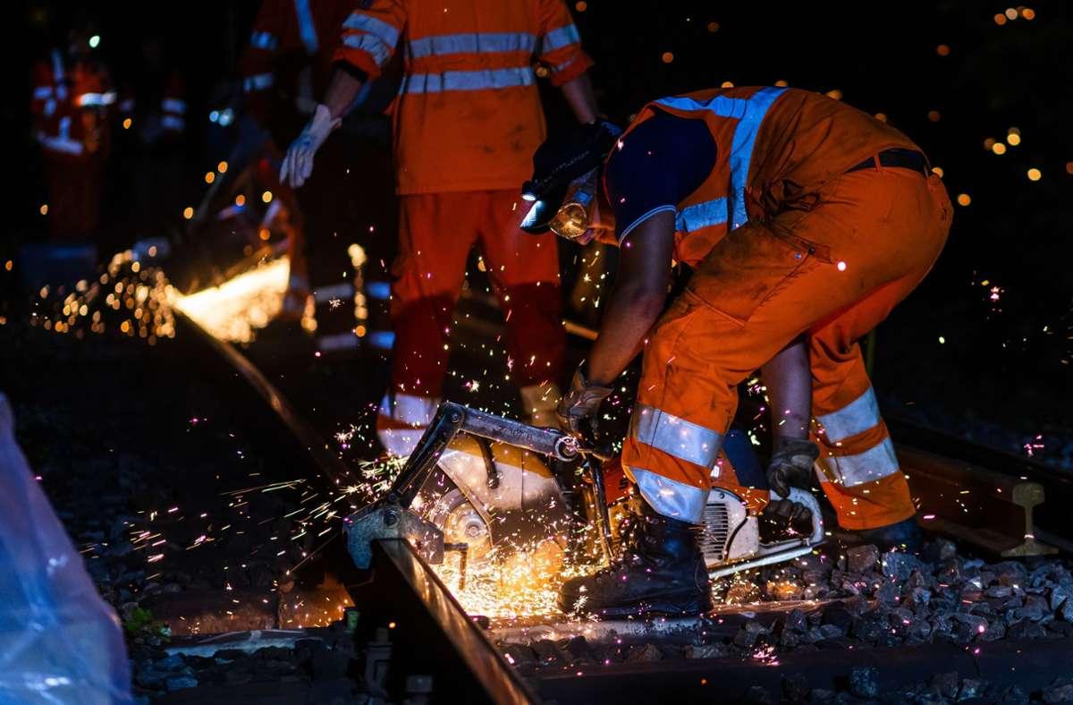 Ein Mitarbeiter der Bahn trennt mit einer Flex ein fehlerhaftes Stück aus einer Schiene heraus. Foto: dpa/Philipp von Ditfurth