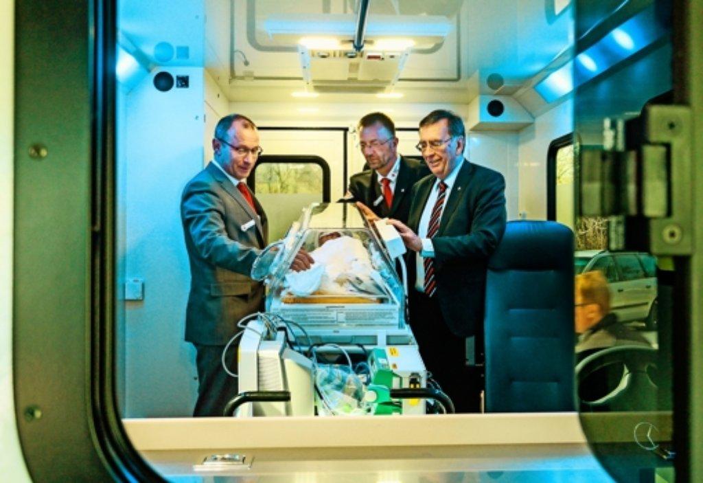 Drei Männer und  – kein Baby: Gerhard Fuchs, Wolfgang Breidbach und Michael Steindorfner  (von links) vom Deutschen Roten Kreuz  präsentieren  den Notarztwagen Foto: factum/Granville