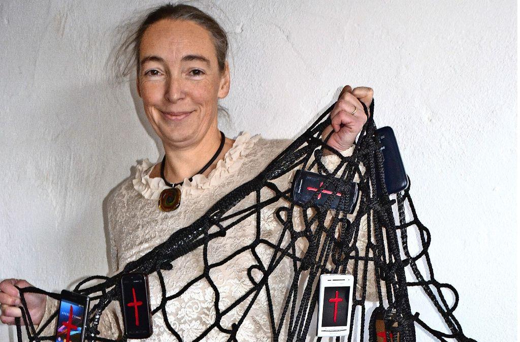 """Marion Musch präsentiert ihre Netzinstallation, an der 36 Handys und Tablets hängen. Diese wird bei der Messe """"Arte-Sono"""" zu sehen sein. Foto: Fatma Tetik"""