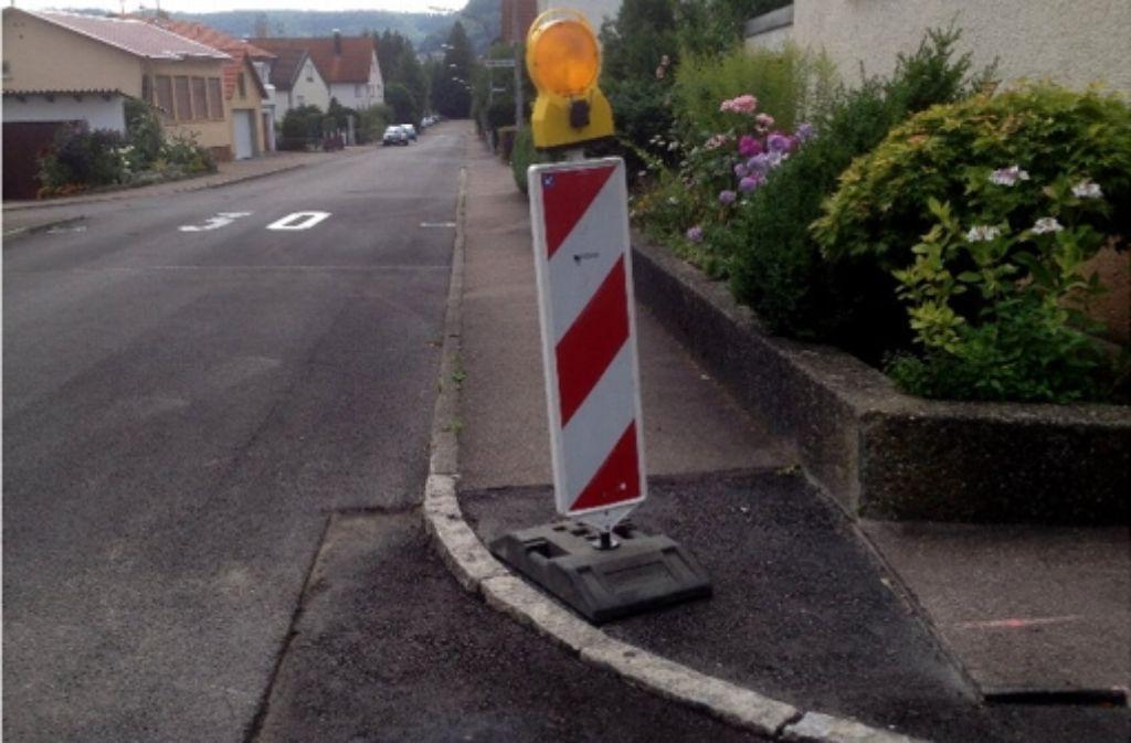 Die Baufirma hat in der Langen Straße ein Loch im Deckbelag und eine Warnbake hinterlassen. Foto: Gemeinde