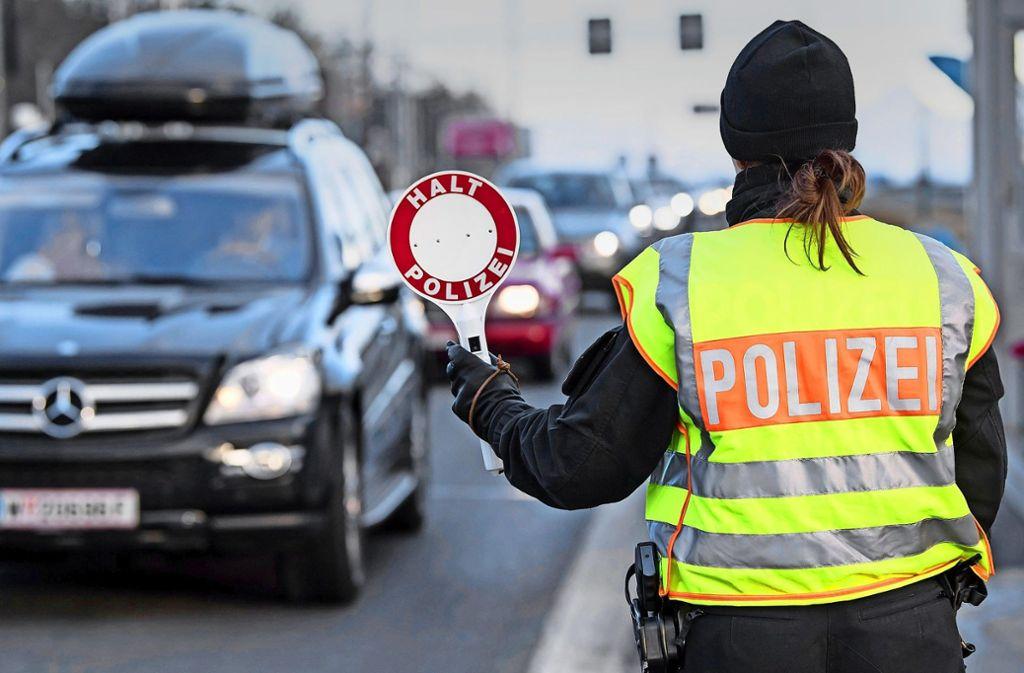 Eine Polizistin winkt an der A8 Salzburg–München Fahrzeuge, die aus Österreich kommen, für eine Kontrolle aus dem Verkehr. Foto: dpa