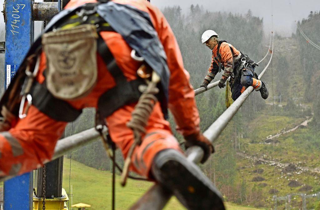 Arbeiter werkeln 2017 an den Tragseilen für die neue Seilbahn zur Zugspitze. In Bayern sind die kontrollierenden Gewerbeaufsichten staatlich geblieben.. Foto: dpa