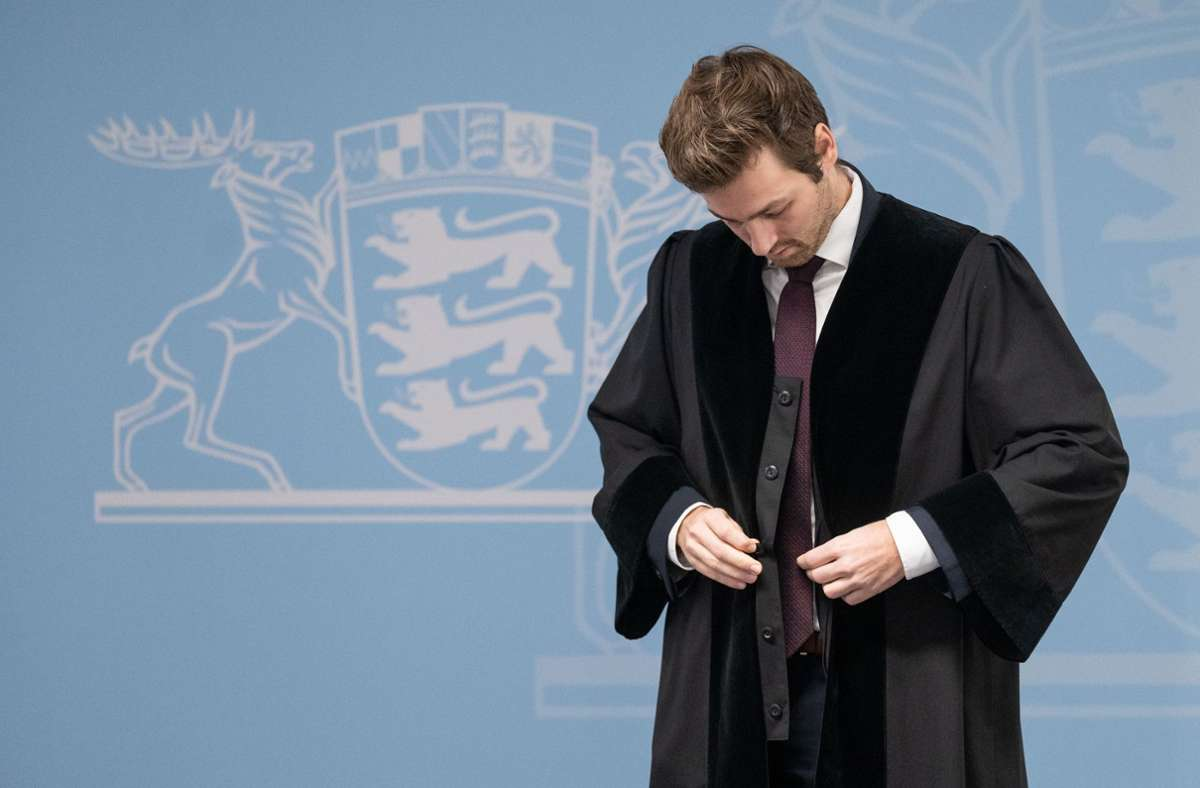 Timo Haußer, Vorsitzender des Landesverbands Baden-Württemberg des Bundes Deutscher Rechtspfleger, legt eine Robe an. Foto: dpa/Marijan Murat