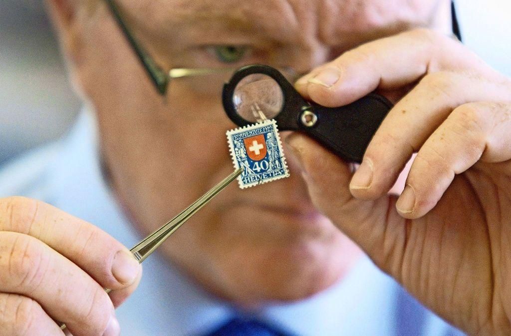 Die gefragten Briefmarken werden genau unter die Lupe genommen. Foto: EPA