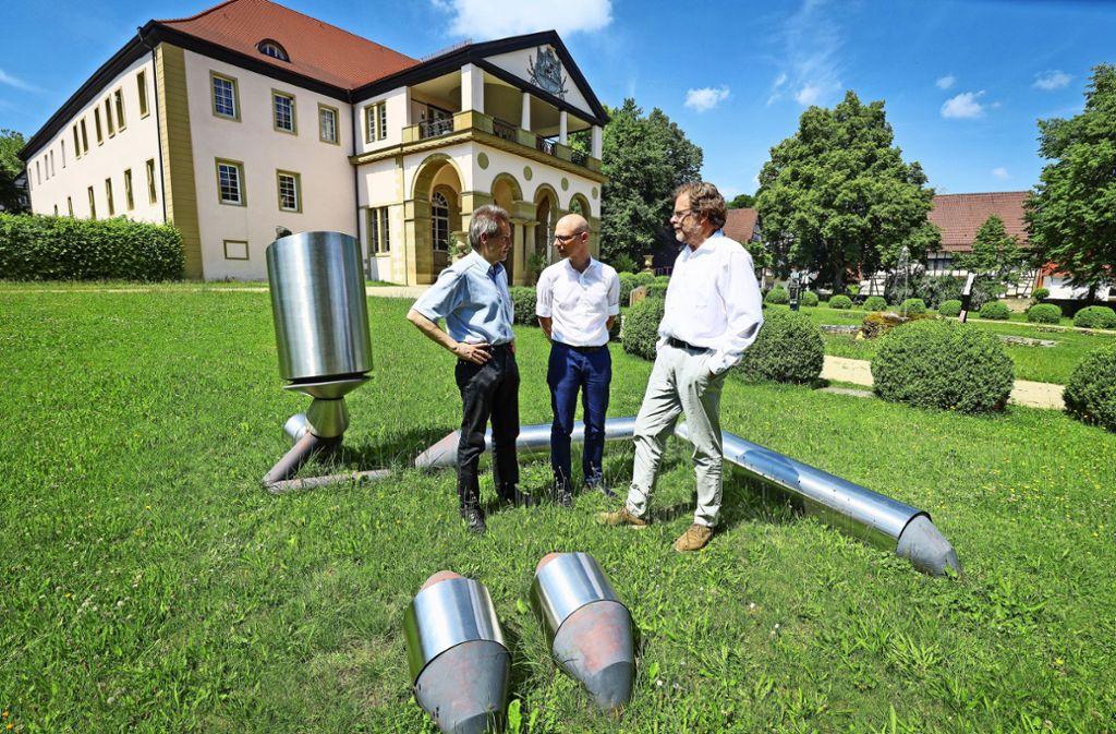 Günter Baumann, Kay Kromeier und Kuno Schlichtenmaier (von rechts) bereiten die Jubiläumsfeierlichkeiten vor. Hier stehen sie vor einer Stahlskulptur der Künstlerin Gerlinde Beck im Garten von Schloss Dätzingen. Foto: factum/Weise
