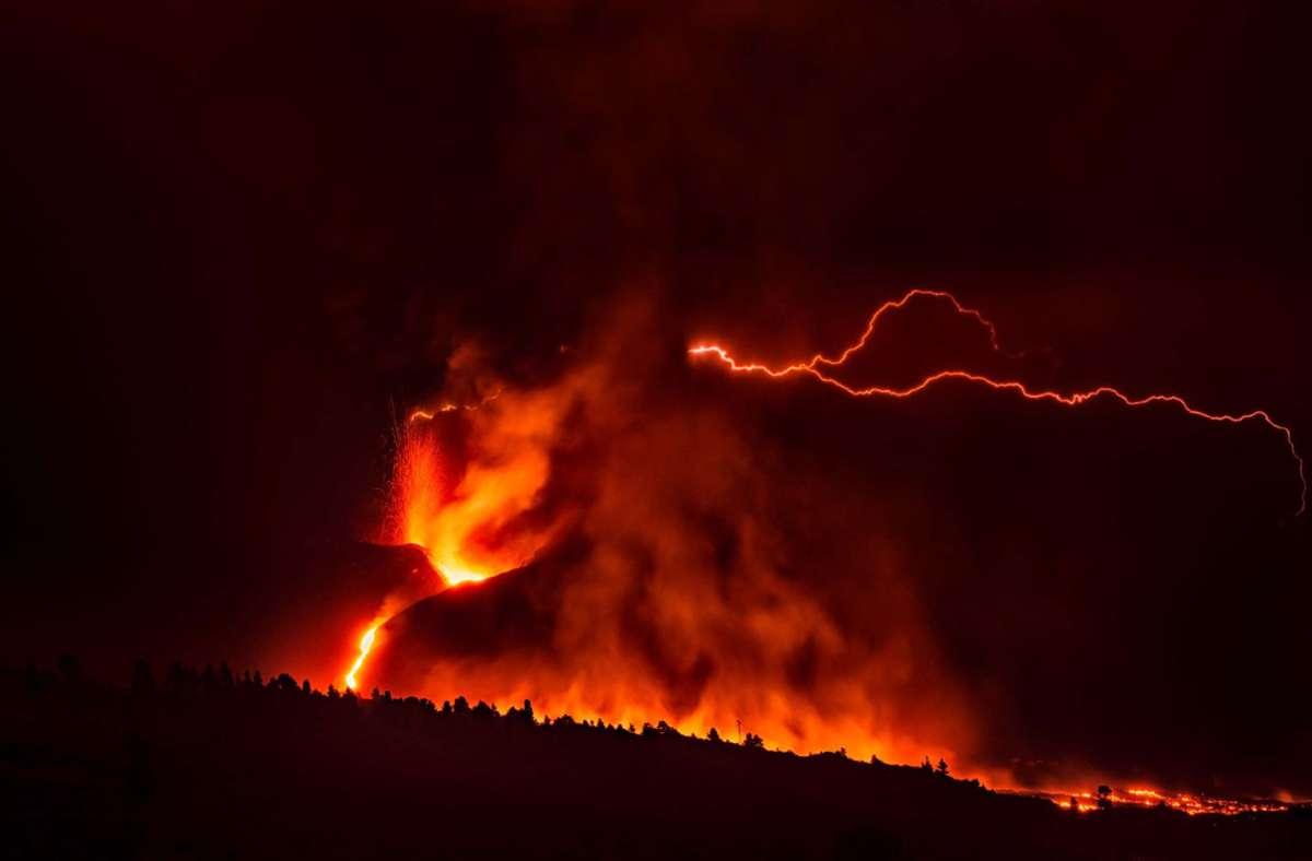 Ein vulkanischer Blitz über dem Vulkan Cumbre Vieja ist trotz des dichten, dunklen Rauchs, der aus dem Krater aufsteigt, von weitem sichtbar. Foto: dpa/Europa Press