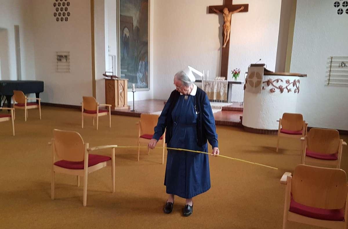 Doris Fuchs misst in der Diakonissenkirche den korrekten Abstand zwischen den Stühlen der Gottesdienstbesucher – fotografiert von Pfarrer Ralf Horndasch. Foto: Ralf Horndasch