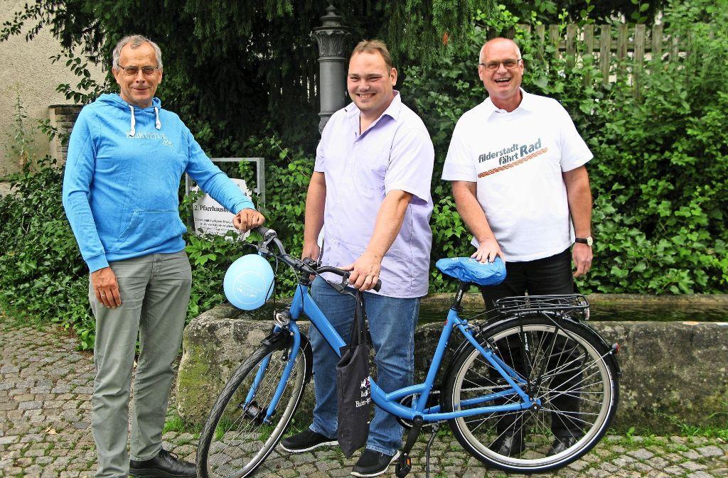 Jürgen Lenz (rechts) und Reinhard Molt (links) übergeben  dem erfolgreichen Schatzjäger Marc Weiss am Plattenhardter Dorfbrunnen das Fahrrad des AGFK. Foto: Götz Schultheiss