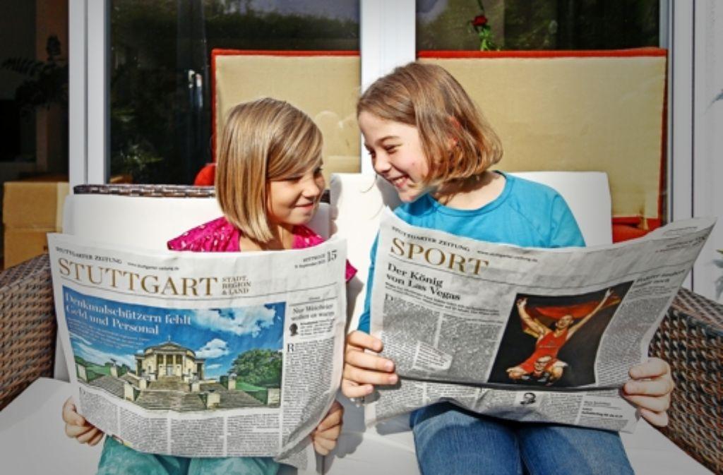 Anna (li., acht Jahre) und Janika (neun Jahre) schmökern in der Stuttgarter Zeitung. Vor allem die Fotos finden sie spannend. Und Geschichten über  Entdeckungen. Foto: factum/Granville