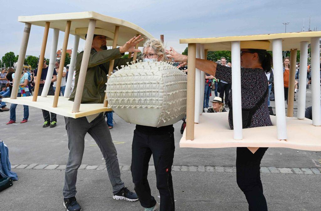 Menschen als Gefängniszellen und Coronavirus: Demonstranten zeigen auf durchaus kreative Art und Weise ihr Anliegen. Foto: AFP/THOMAS KIENZLE