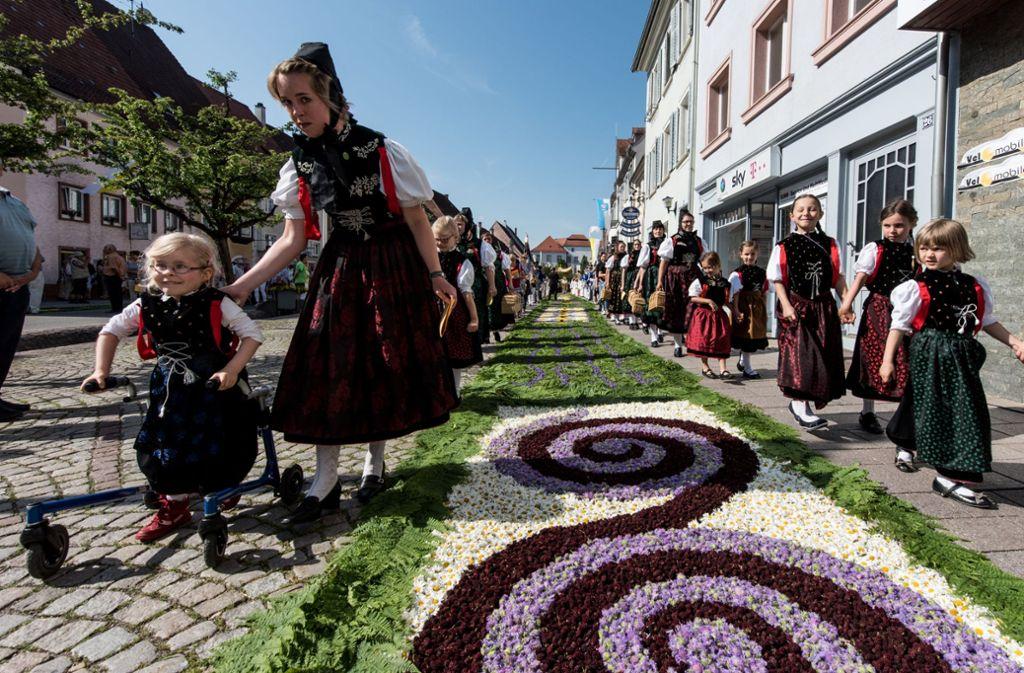 Im  baden-württembergischen  Hüfingen ziehen  Trachtenträgerinnen  an Fronleichnam 2017  während der Prozession an einem prächtig geschmückten Blumenteppich vorbei. Foto: Patrick Seeger/dpa