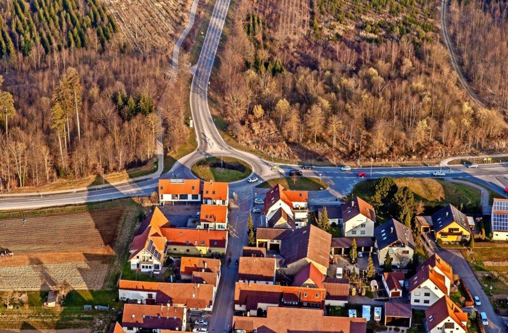 Östlich des  jetzigen Kreisverkehrs in Perouse, wo jetzt noch Wald ist (oben rechts),   wird die neue Ortsumfahrung   mit dem   wichtigen Lärmschutzwall   verlaufen.  Dort angesiedelt wird auch der von Netto    geplante Lebensmittelmarkt. Foto: Archiv
