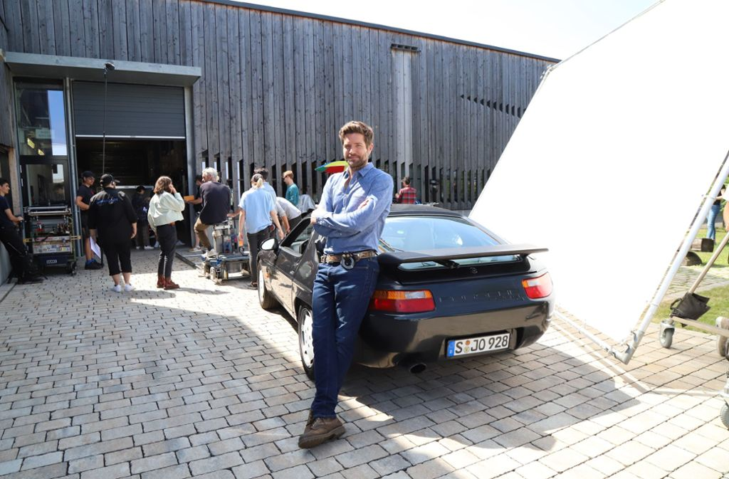 Soko-Stuttgart-Star Peter Ketnath lehnt sich in einer Drehpause in Rommelshausen an seinen Porsche 928. Foto: Patricia Sigerist