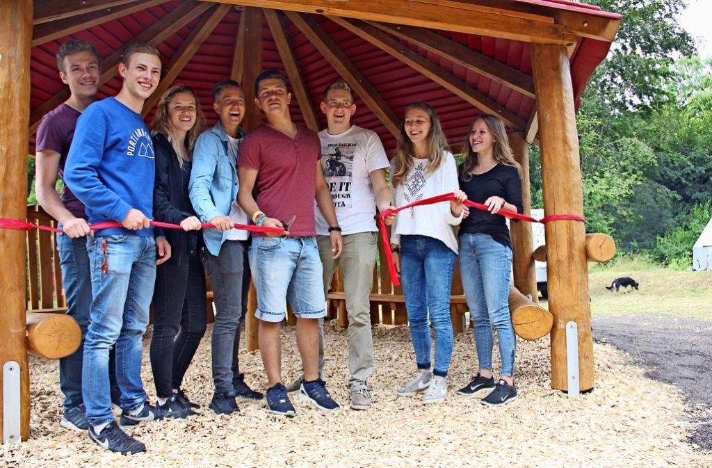 Patrick Steinwand (mit Schere) durchschneidet zusammen mit anderen Jugendlichen das Eröffnungsband für den Holzpavillon. Foto: Bernd Zeyer