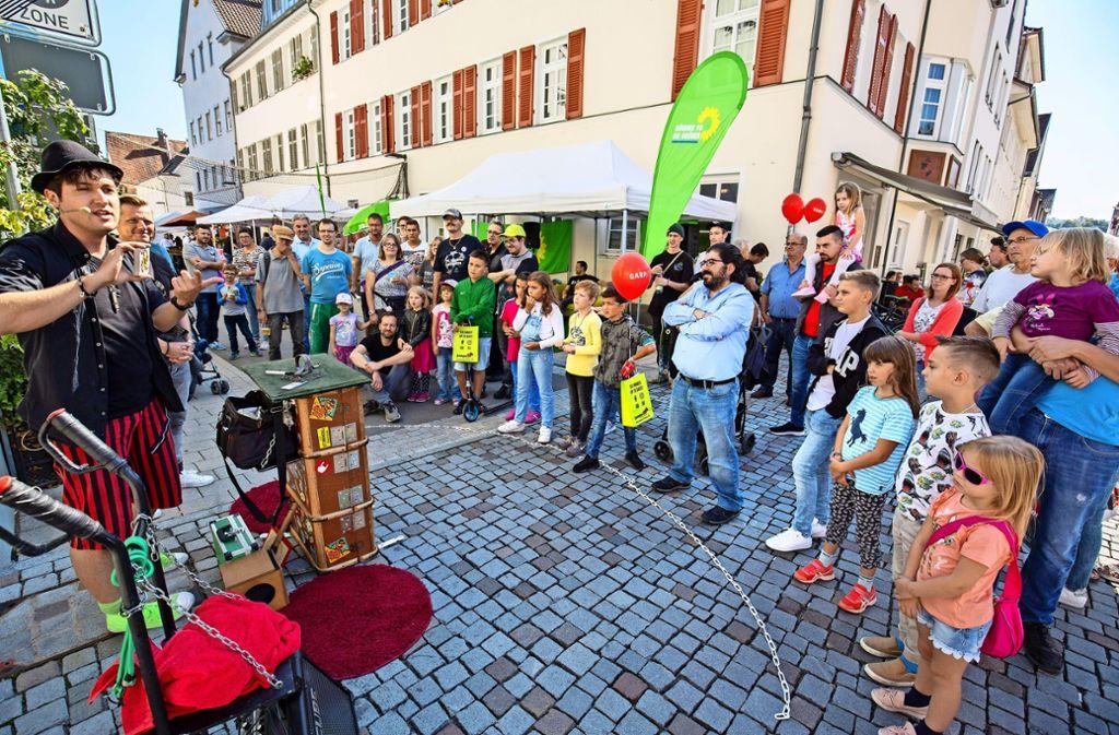 Ein Straßenkünstler unterhält die Passanten beim Stadtfest mit Zaubertricks. Foto: Michael Steinert