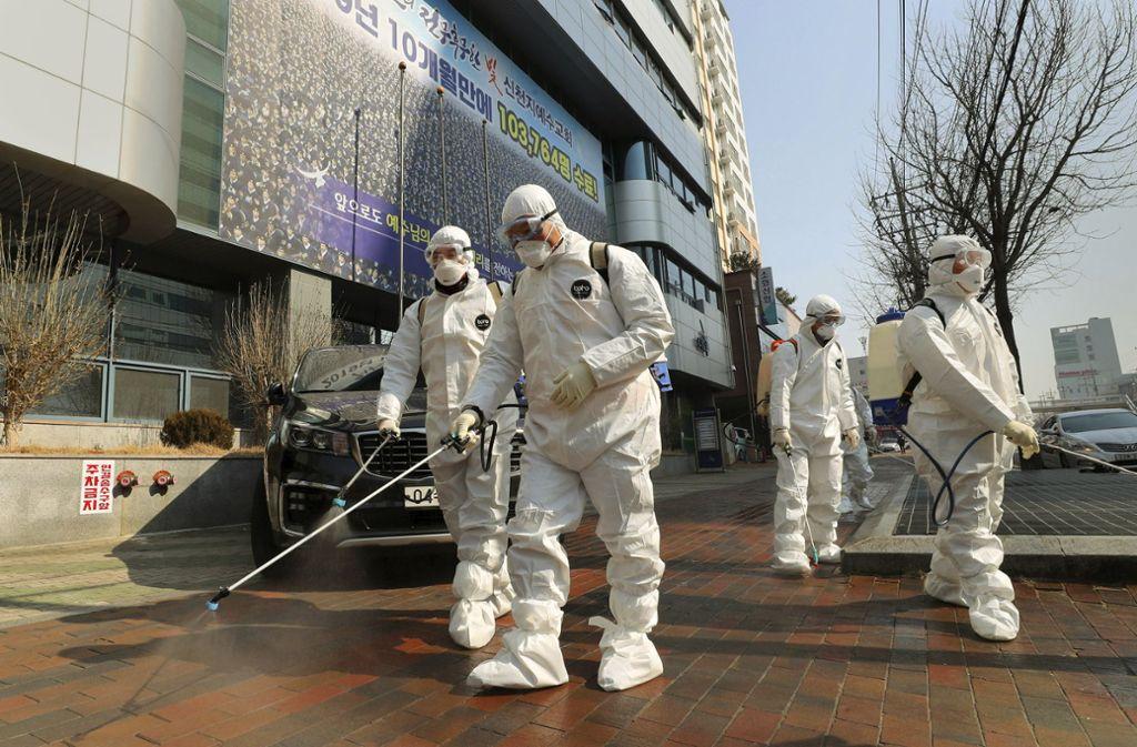 Kampf gegen das Coronavirus im südkoreanischen Daegu: Arbeiter in Schutzkleidung desinfizieren den Straßenraum vor einem Gotteshaus. Foto: dpa/Kim Jun-Beom