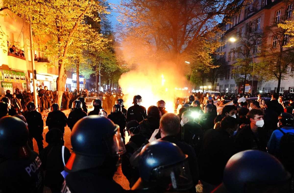 """Polizisten stehen am Rande der Demonstration linker und linksradikaler Gruppen unter dem Motto """"Demonstration zum revolutionären 1. Mai"""" vor einem Feuer auf der Straße. Foto: dpa/Kay Nietfeld"""
