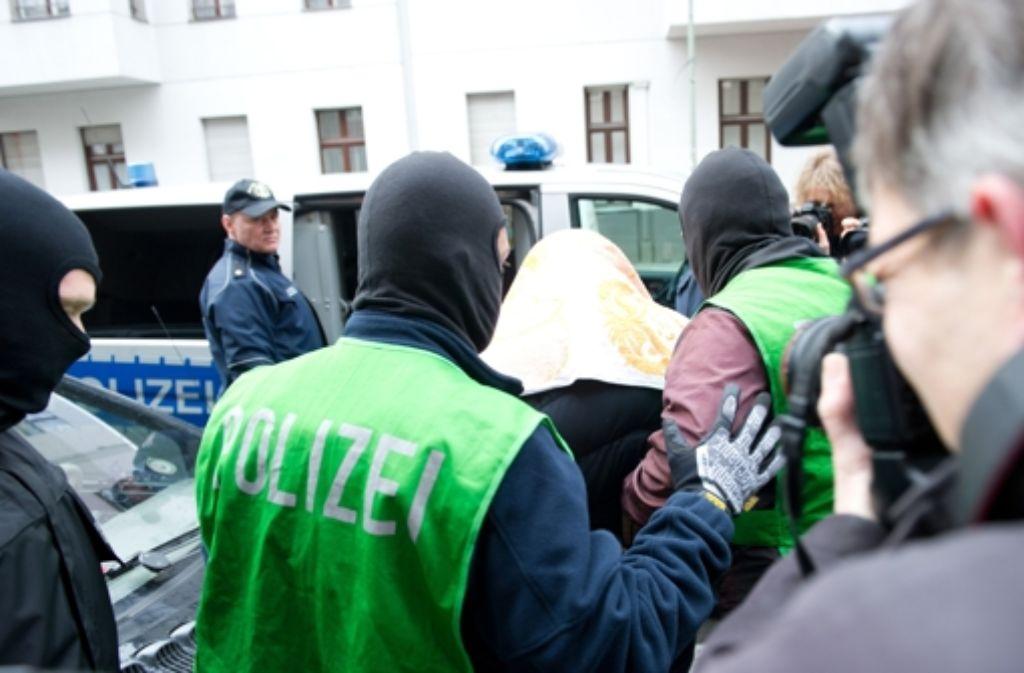 Zugriff in der Hauptstadt: Polizisten führen bei einer Razzia gegen Islamisten in Berlin einen mit einem Tuch verdeckten Verdächtigen ab. Foto: dpa