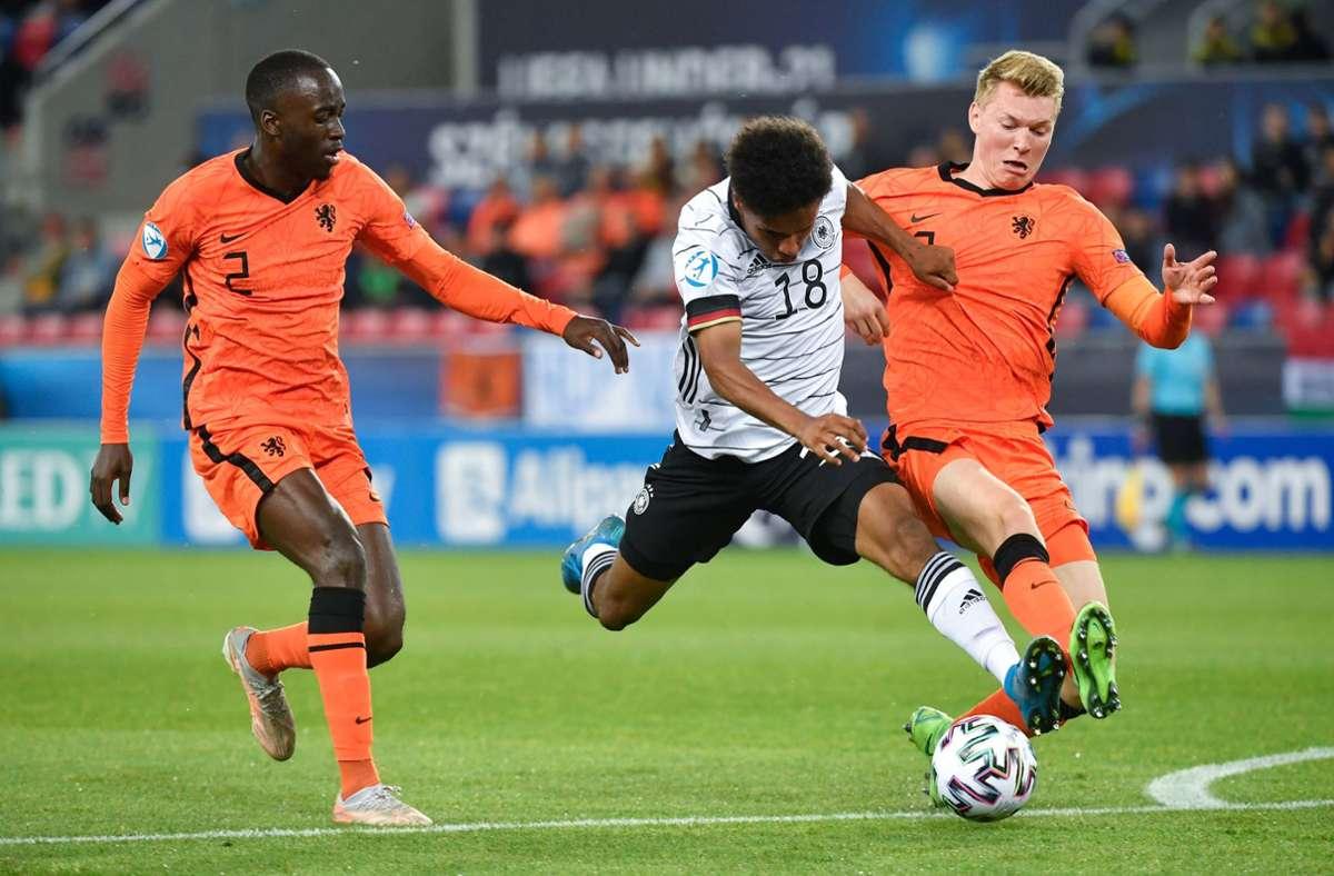 Karim-David Adeyemi (M) von Deutschland und Jordan Teze (l) und Perr Schuurs von den Niederlanden kämpfen um den Ball. Foto: dpa/Marton Monus