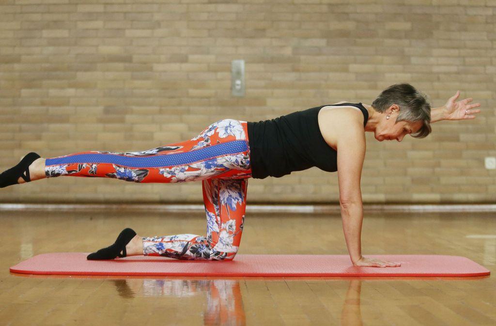 Bauchnabel einziehen und rechtes Bein auf Höhe der Hüfte nach hinten strecken. Dann langsam den linken Arm nach vorne strecken. Die Position drei bis fünf Atemzüge halten. Foto:  Baumann