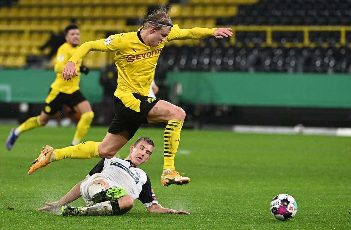 Erling  Haaland (l.) und  Paderborns Uwe Huenemeier im Duell Foto: AFP/INA FASSBENDER