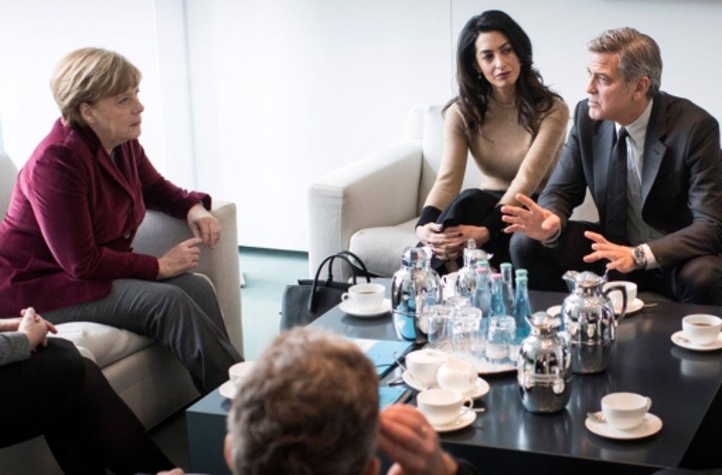 George Clooney (r.) und seine Frau Amal (Mitte) haben sich mit Angela Merkel (l.) getroffen. Foto: dpa/Bundespresseamt