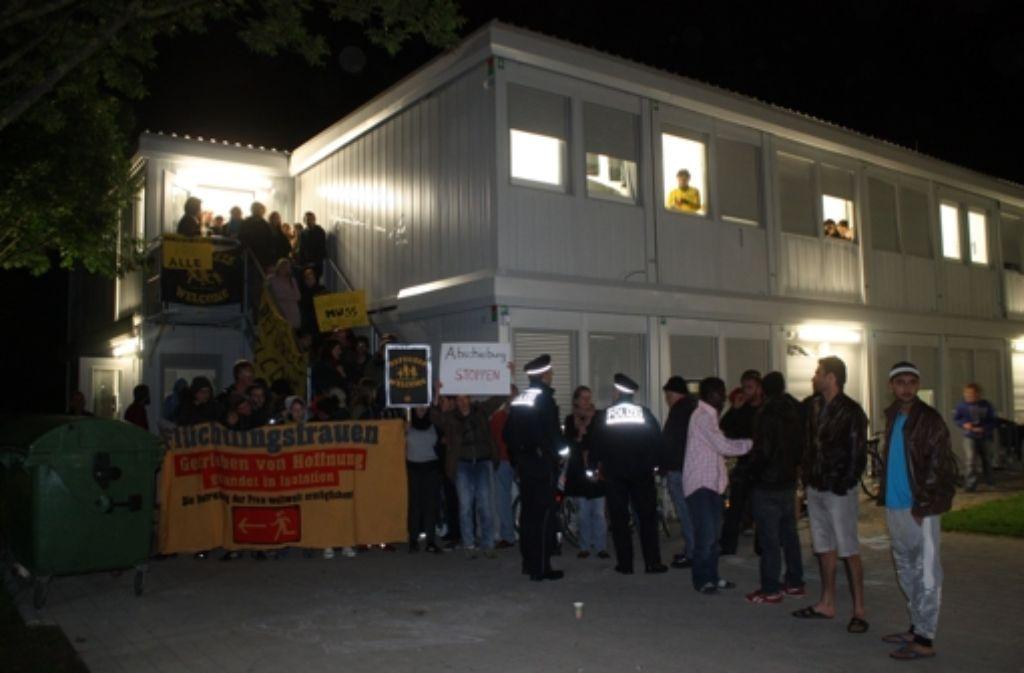 Mit einer friedlichen Blockade verhindern Ehrenamtliche vom Freundeskreis für Flüchtlinge und ihre Unterstützer, dass die Polizei zu einem von Abschiebung bedrohten Gambier vordringen kann. Foto: Eva Herschmann