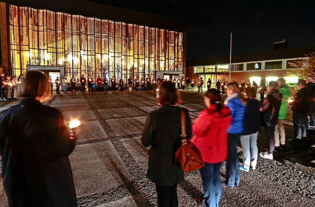 80 Menschen stehen schweigend im Kreis vor der erleuchteten Christuskirche: Protest gegen Stellenkürzung in Korntal. Foto: factum/Bach