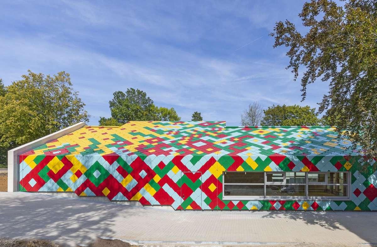Viel Farbe für Fassade und Dach: Die Töne Ginstergelb, Karminrot, Minzgrün und Pastelltürkis formen ein fröhliches Muster, das an eine sonnenbeschienene Blumenwiese erinnert. Foto: W.-D. Gericke