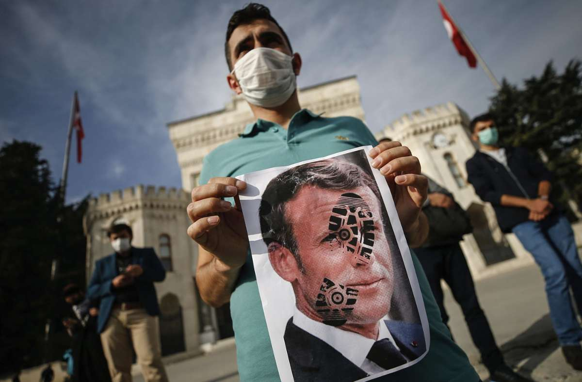 Einjunger Mann hält in Istanbul das Foto des französischen Präsidenten in den Händen. Er protestiert damit gegen die Islam-kritischen Äußerungen des Staatschefs. Foto: dpa/Emrah Gurel