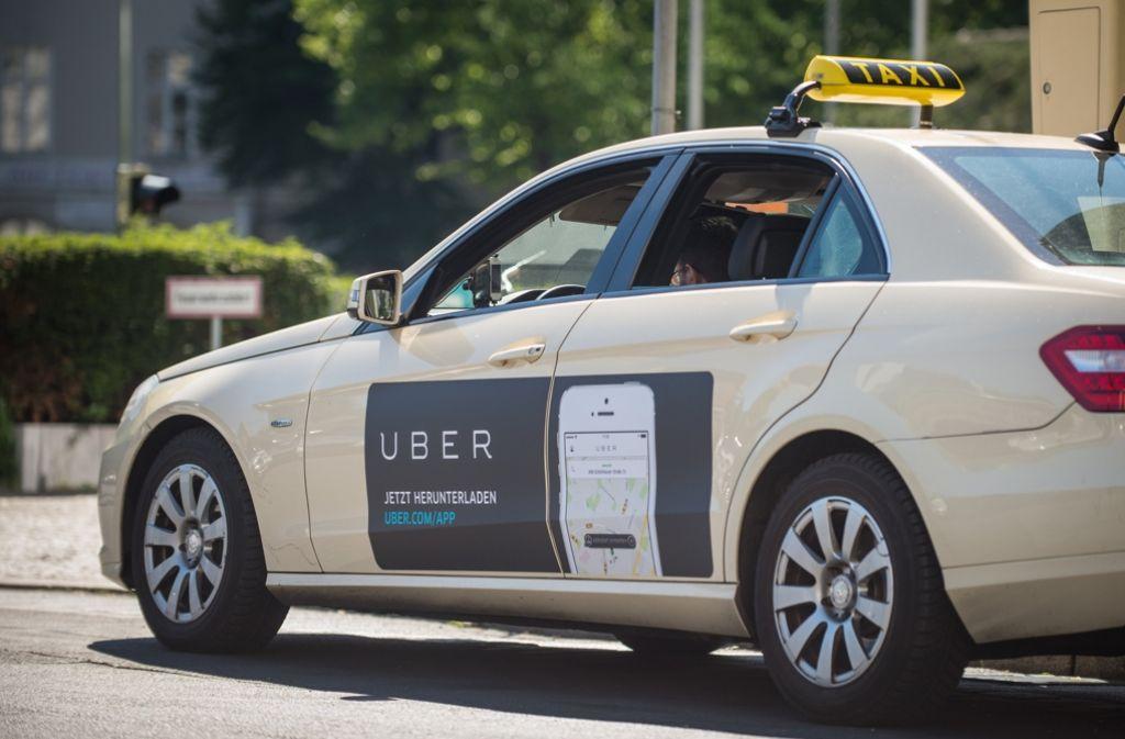 Ein Taxi mit einer Werbung für die Uber-App. Foto: dpa