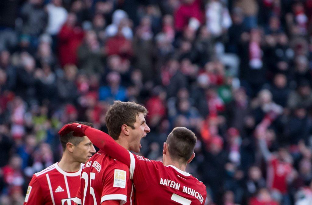 Robert Lewandowski (l-r), Torschütze Thomas Müller und Franck Ribery von München jubeln über das Tor zum 1:1. Foto: dpa