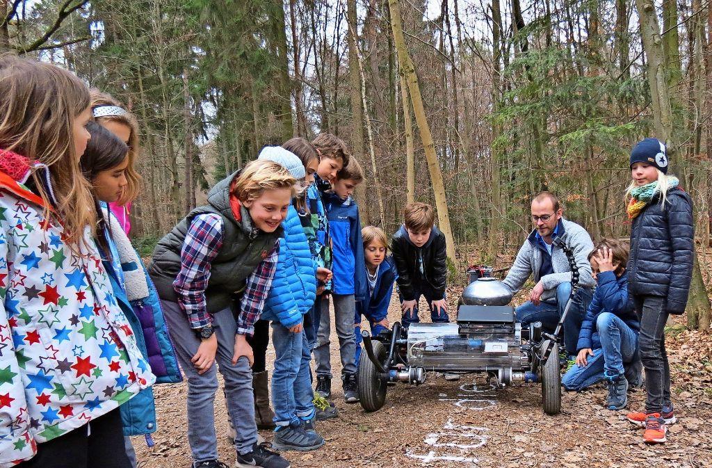 Schüler der Wilhelm-Hauff-Schule beobachten den niederländischen Künstler Gijs van Bon und seinen selbst gebauten Roboter bei der Arbeit. Foto: Julia Bosch