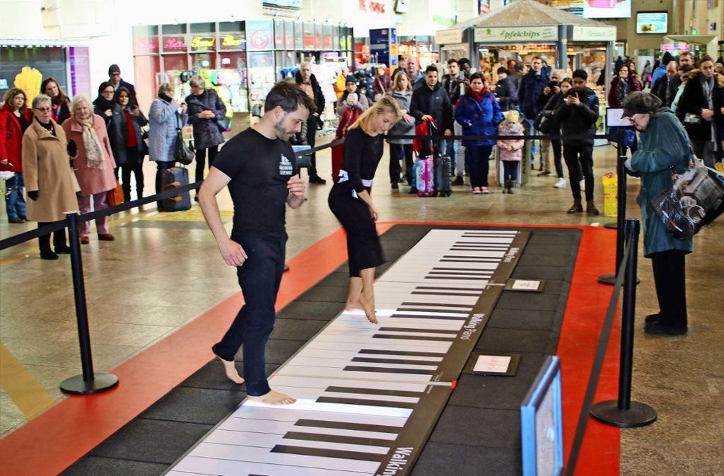 Dennis Volk und Leslie Lynn tanzen auf dem Walking Piano für die Reisenden in der Bahnhofshalle. Die beiden Künstler wollen den Zuschauern eine Auszeit vom Alltag verschaffen. Foto: Julia Schenkenhofer