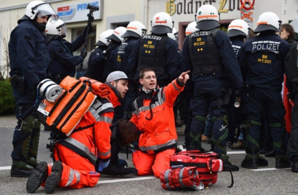 Sanitäter kümmern sich in Weinheim während des NPD-Bundesparteitages um eine auf dem Boden liegende Gegendemonstrantin. Foto: dpa