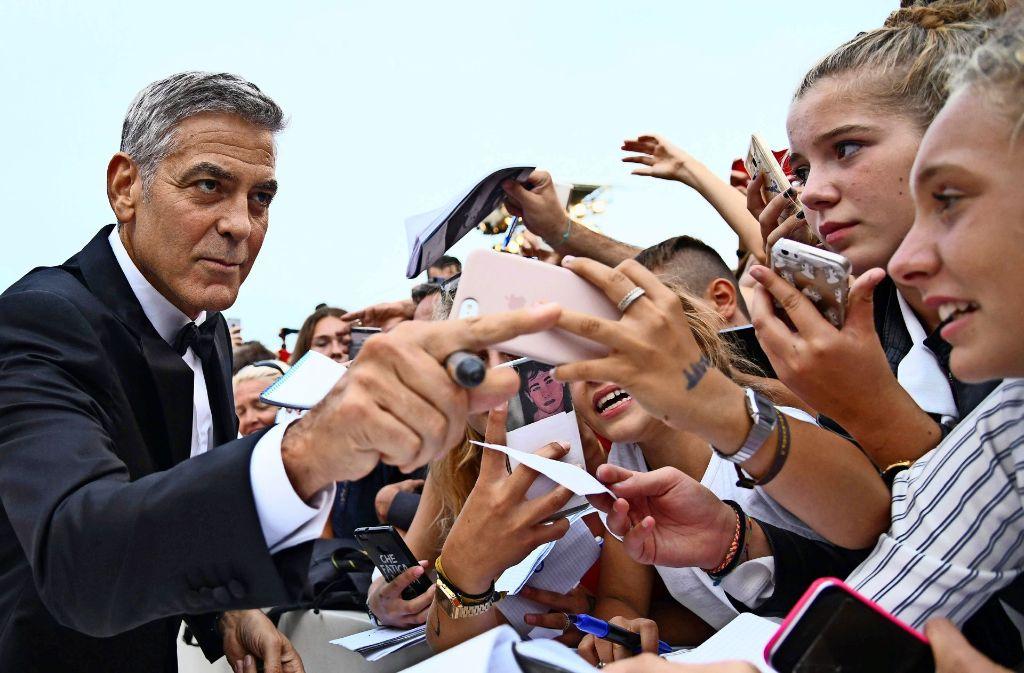 """Wo er auftaucht, herrscht Hysterie: George Clooney verteilt am Lido Autogramme vor der Premiere seines Films """"Suburbicon"""" Foto: AFP/Filippo Monteforte"""