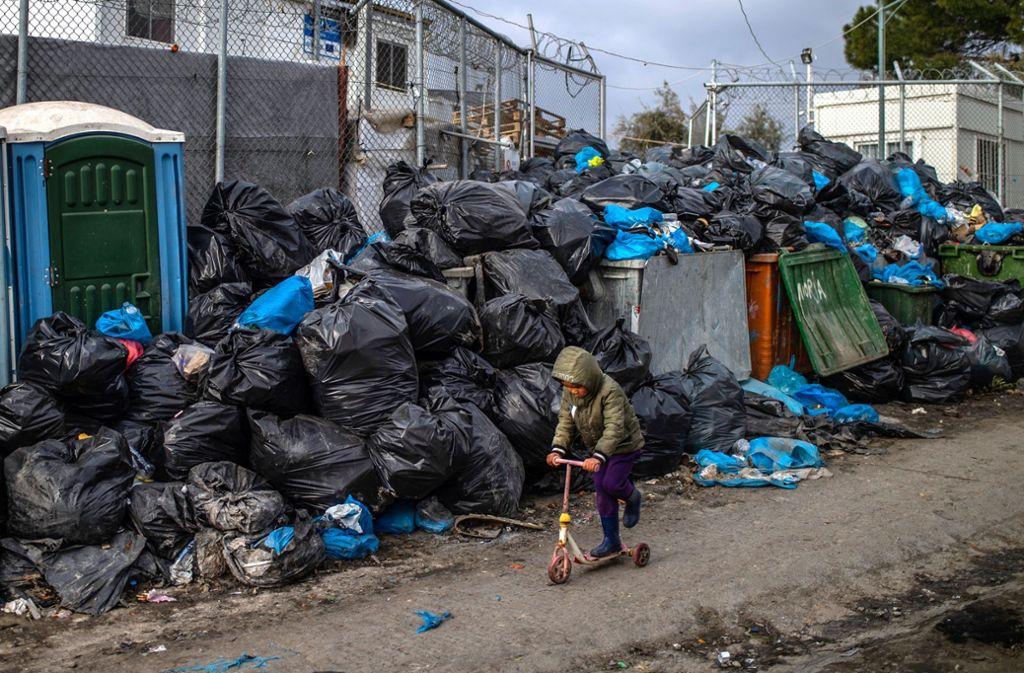 Ein Flüchtlingsjunge fährt mit einem Roller vor Müllsäcken im Flüchtlingslager Moria auf Lesbos. (Archivbild) Foto: dpa/Angelos Tzortzinis