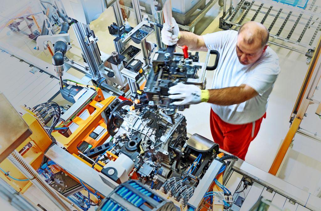 Ein Audi-Mitarbeiter montiert im ungarischen Györ  einen Elektromotor. Foto: Audi