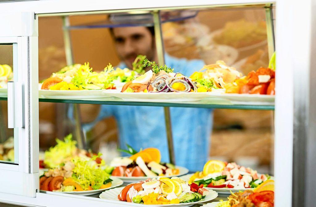 Ein Kantinenmitarbeiter schiebt zubereitete Salate in die Auslage. Foto: imago stock&people/imago stock&people