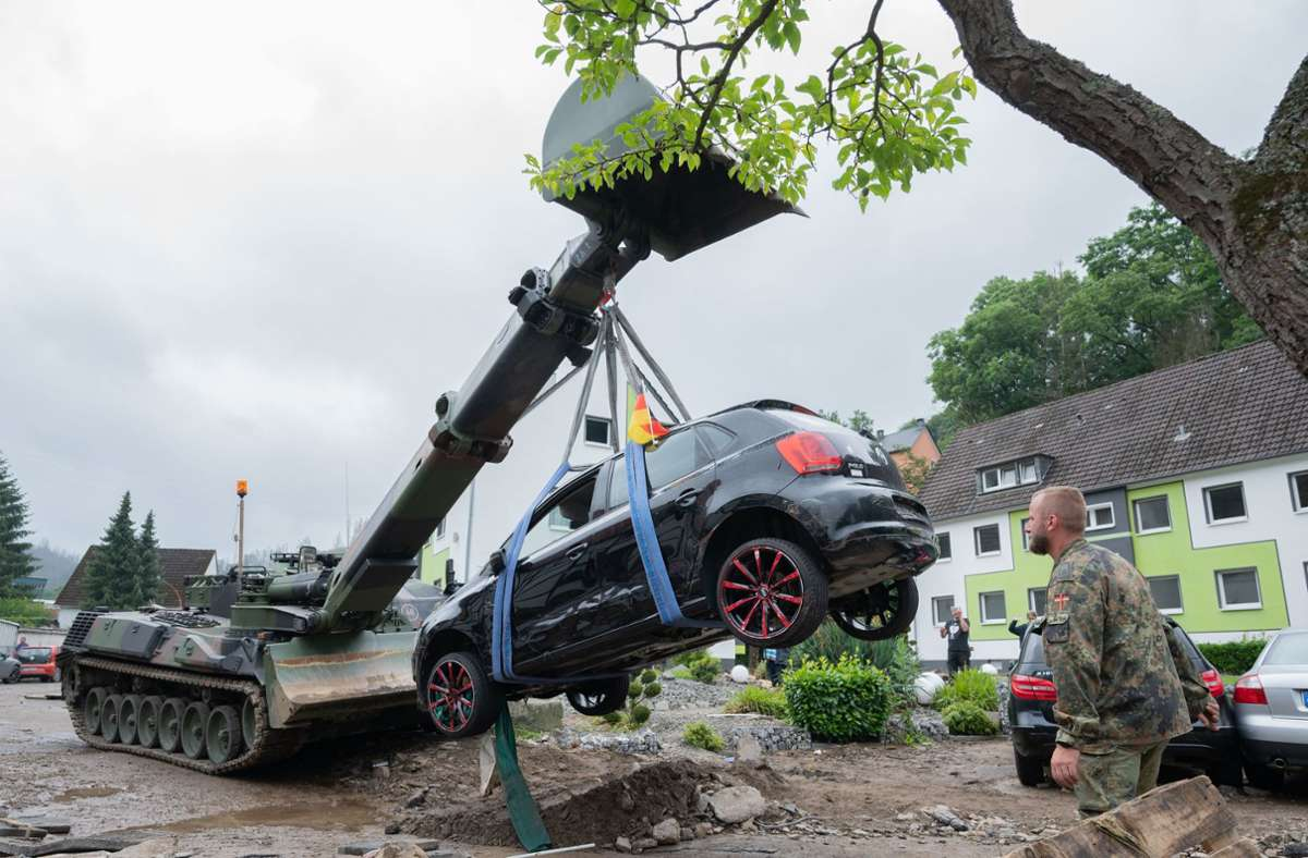 Soldaten der Bundeswehr bergen mit einem Panzer ein bei den Unwettern zerstörtes Auto. Foto: dpa/Julian Stratenschulte