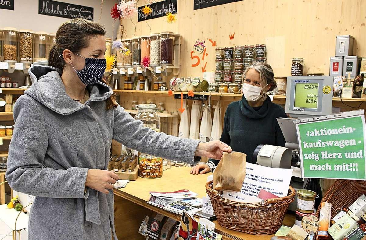 Die Kundin Irene Sperl-Schreiber legt eine Sachspende in einen Sammelkorb im Sillenbucher Laden Tante M, die Inhaberin Maarit Schneider-Penna freut sich. Foto: Holowiecki