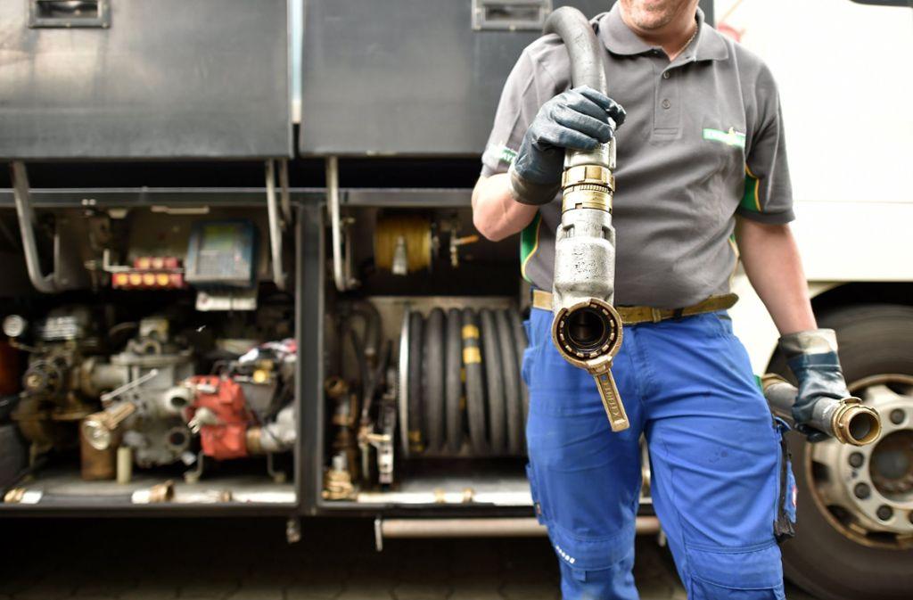 Ein Heizöl-Tankwagenfahrer zieht den Schlauch zum Betanken mit Heizöl zu einem Mehrfamilienhaus. Foto: dpa