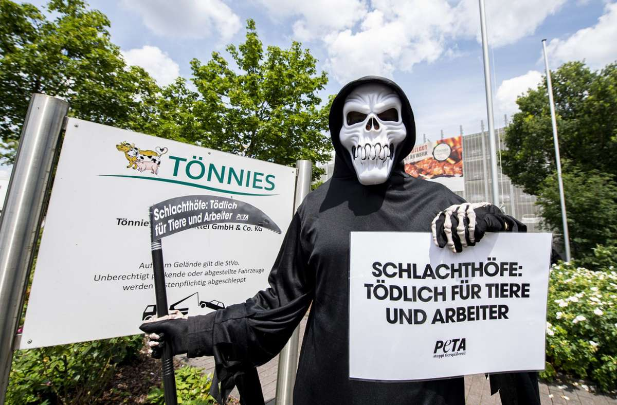 Ein als Tod verkleideter Aktivist der Tierschutzorganisation Peta demonstriert mit einer Sensenatrappe vor dem Firmengelände von Tönnies. Foto: dpa/David Inderlied