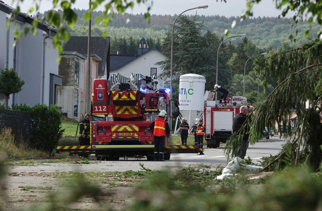 Nach dem  schweren Unwetter mit einem Tornado räumen Feuerwehrleute  in der  Stadt Pettingen im Südwesten Luxemburgs  eine Straße frei. Mehrere Menschen wurden durch die Folgen des Unwetters nach Angaben der luxemburgischen Regierung verletzt –  einige davon schwer.. Foto: Harald Tittel/dpa